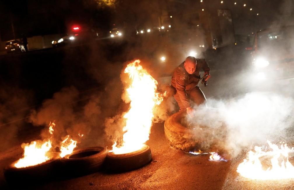 Policial tira pneu de barricada em chamas durante protesto na Rodovia Presidente Dutra, em São Paulo, no início da manhã desta sexta-feira (28)  (Foto: Nacho Doce/Reuters)