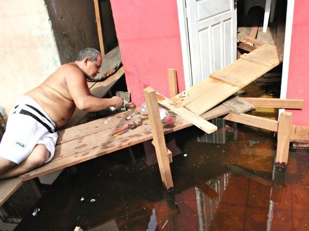 Morador conserta tubulação deteriorada pela água (Foto: Marcos Dantas / G1 AM)
