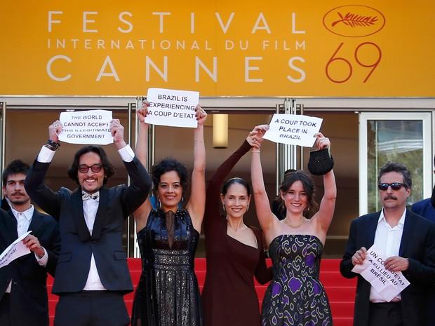O director Kleber Mendonça Filho e membros do elenco do filme 'Aquarius' exibem cartazes contra o processo de impeachment da presidente afastada Dilma Rousseff durante chegada no tapete vermelho do festival de Cannes, na França (Foto: Yves Herman/Reuters)