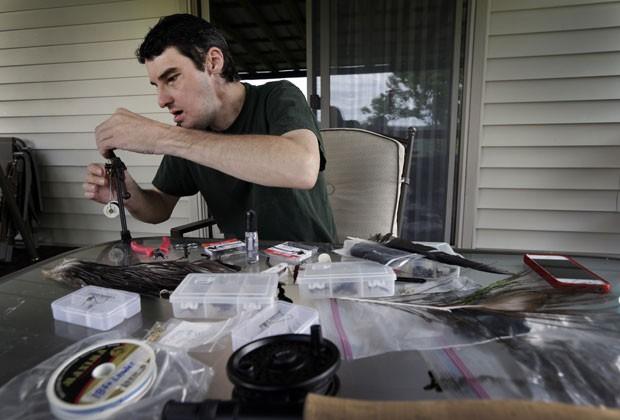 Richard Norris trabalha com material de pesca em foto de 25 de junho (Foto: Chuck Burton/AP)