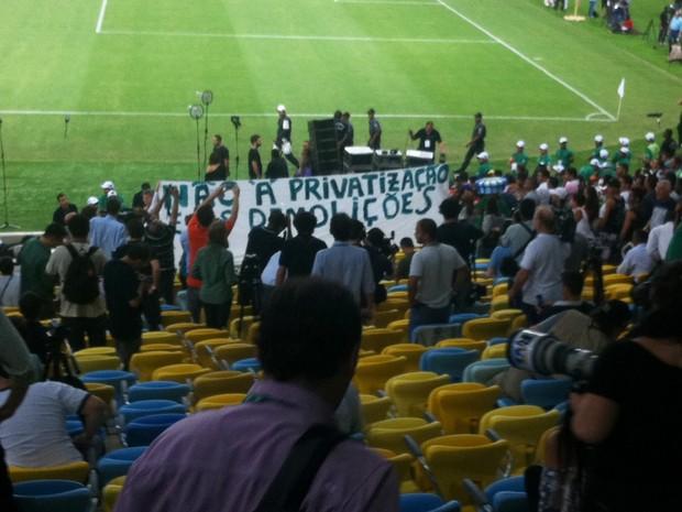 Mesmo dentro do estádio, integrantes de um comitê popular protestaram com uma faixa contra a privatização e demolições (Foto: Lívia Torres/G1)