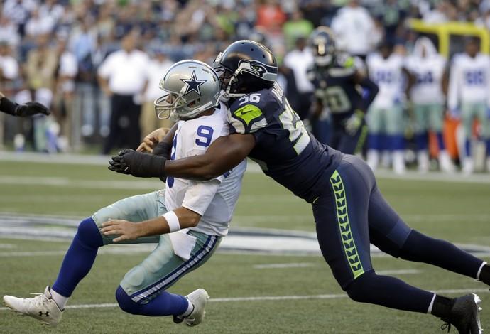 Cliff Avril atinge Tony Romo pelas costas no confronto entre Seahawks e Cowboys (Foto: AP)