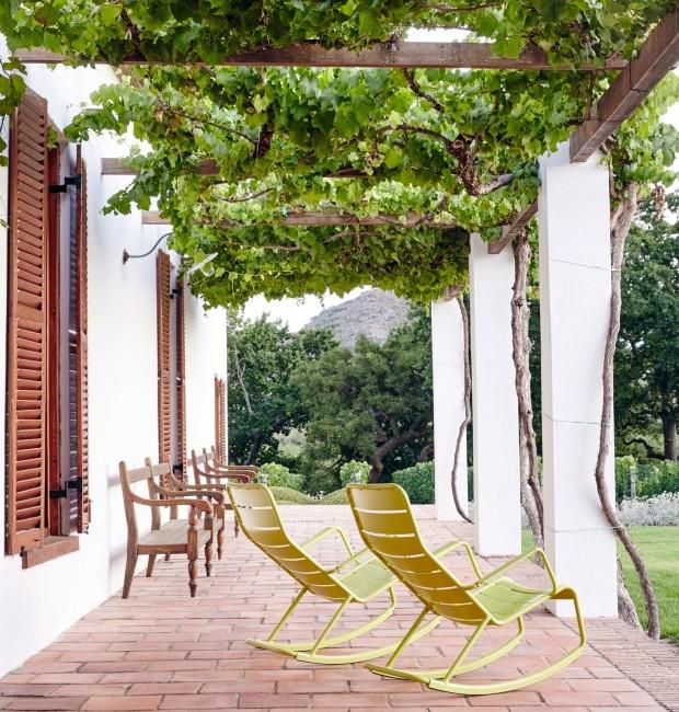 Varanda. Posicionadas com vista para o jardim, as cadeiras de balanço Luxembourg, de Frédéric Sofia para a Fermob, são recobertas pela pérgola de folhas de uva (Foto: Greg Cox / Bureaux)