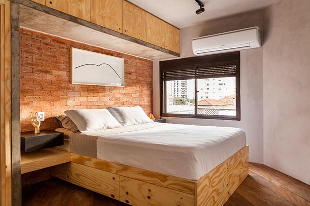 A cama de pinus maciço foi desenhada pela Tripper Arquitetura e executada pela Marcenaria Marcen Mello. Ao fundo, uma parede de tijolos da Pasinato, modelo stromboli, completa o mix de revestimentos do ambiente (Foto: Julia Ribeiro/Divulgação)