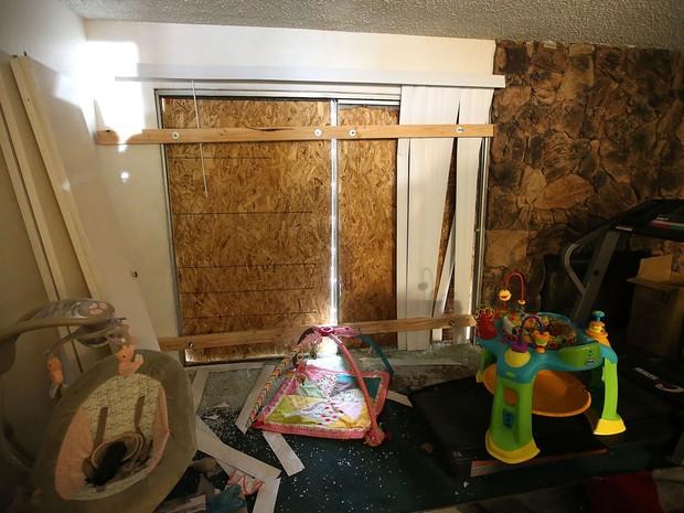 Quarto com janelas bloqueadas por tábuas de madeira na casa dos suspeitos no tiroteio de San Bernardino, Syed Farook e Tashfeen Malik, fotografado durante visita da imprensa na sexta (4) (Foto: Justin Sullivan/Getty Images/AFP)
