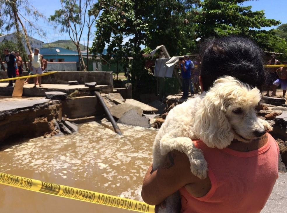 Mulher recolher cão após alagmento  (Foto: Matheus Rodrigues/G1)