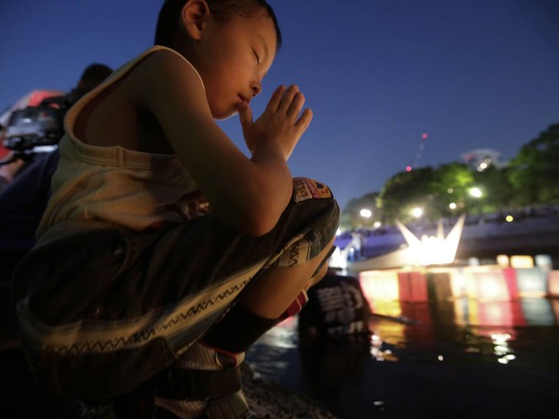 Menino faz oração após colocar uma lanterna japonesa de papel no rio Motoyasu, diante do Domo da Bomba Atômica em Hiroshima, durante memorial dos 70 anos da explosão da bomba que deixou 140 mil mortos na cidade ao fim da II Guerra Mundial (Foto: Eugene Hoshiko/AP)