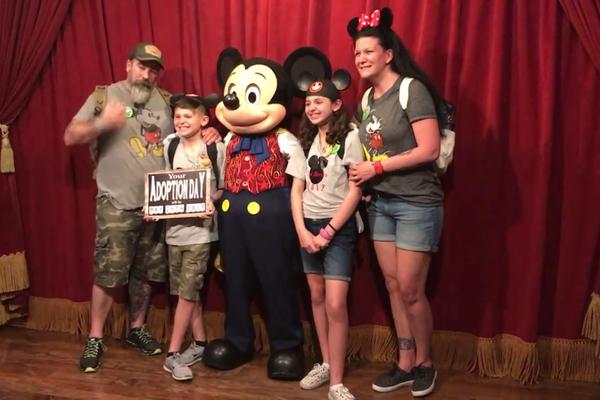 O personagem Mickey Mouse da Disney com a família emocionada com a notícia da adoção (Foto: Facebook)
