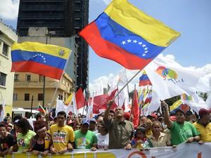"""Ministro do Ministério da Educação da Venezuela, Hector Rodriguez (centro), acena com a bandeira venezuelana durante o """"Grande Março da Juventude e Paz"""", manifestação em Caracas ocorrida neste sábado (15) (Foto: LEO RAMIREZ/AFP)"""