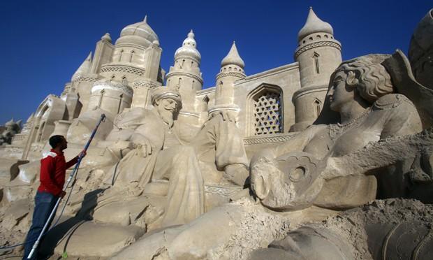 Homem trabalha em escultura em vilarejo de areia no Kuwait (Foto: Yasser Al-Zayyat/AFP)