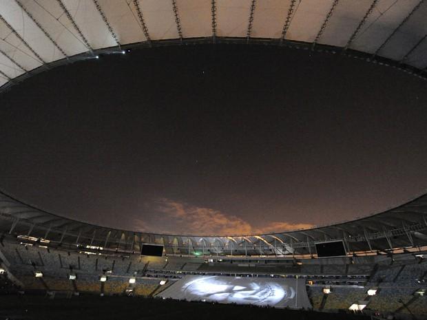 Estádio foi parcialmente apagado para a exibição de um vídeo antes no início da cerimônia (Foto: Vanderlei Almeida / AFP)