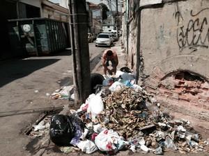 Morador da Rua Presidente Barroso, na Cidade Nova, coloca mais um saco de lixo na pilha da calçada, esquina com a Avenida Salvador de Sá. (Foto: Guilherme Brito / G1)