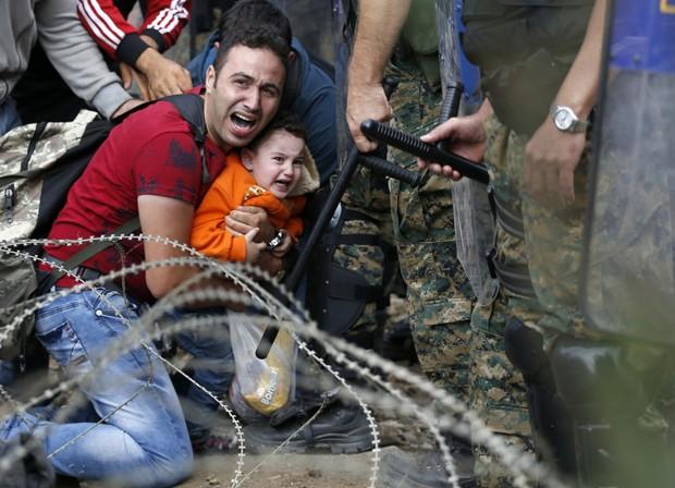 Migrante protege criança perto da estação ferroviária de fronteira Idomeni, norte da Grécia, durante conflito com forças de segurança da Macedônia nesta sexta-feira (21) (Foto: Darko Vojinovic / AP)