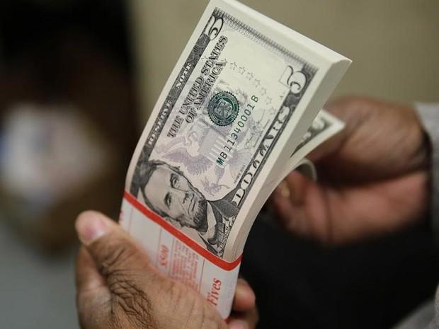 Maço de dinheiro com notas de US$ 5, dólar no câmbio (Foto: Gary Cameron/Reuters)