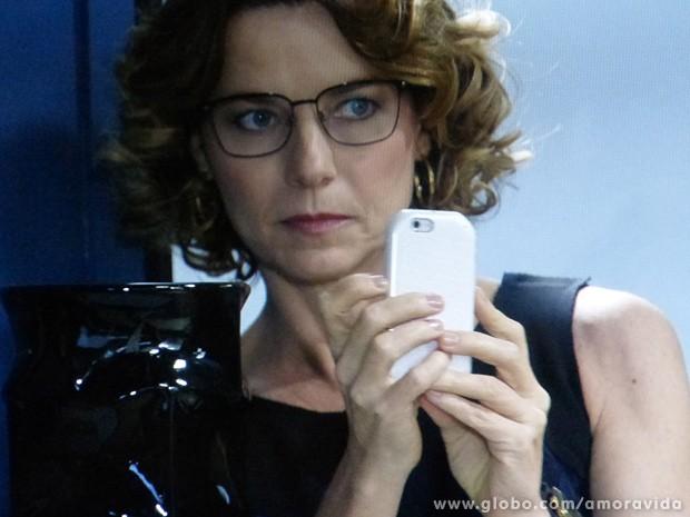 Ela tirava fotos do vilão com seu telefone (Foto: Amor à Vida / TV Globo)
