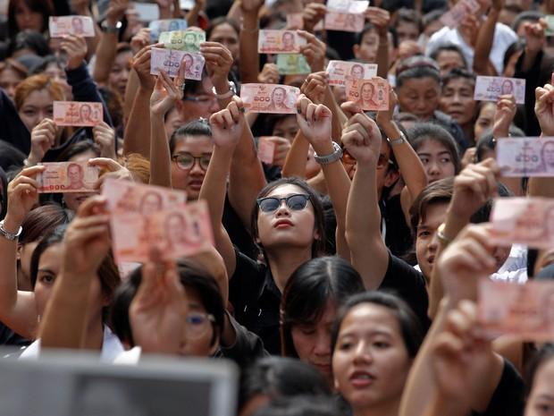 Tailandeses mostram retrato do Bhumibol Adulyadej, que morreu na quinta-feira (13), nas cédulas da moeda local, o baht. Eles aguardavam a saída do corpo do hospital (Foto: Chaiwat Subprasom/ Reuters)