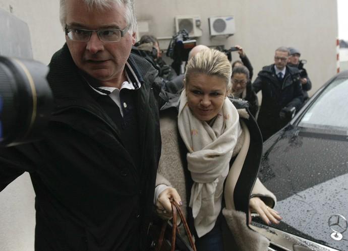 Corinna Schumacher tenta fugir das câmeras na chegada ao hospital no sábado onde Michael está internado (Foto: AP)