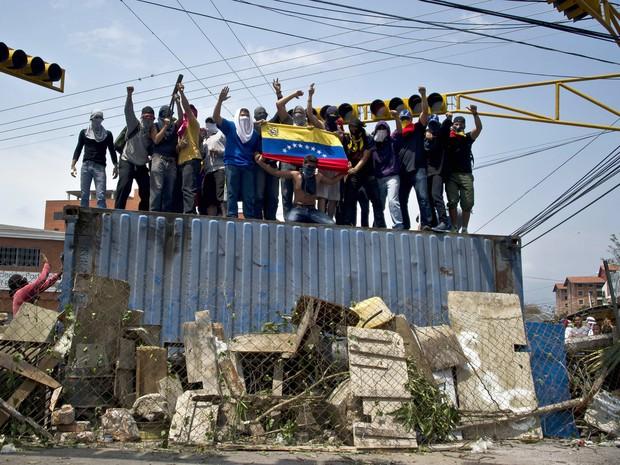 Manifestantes sobem em conteiner para protestar contra Nicolás Maduro na capital de Tachira, na Venezuela. (Foto: Luis Robayo/AFP)