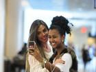 De vestidinho branco, Nicole Bahls posa com fãs em aeroporto