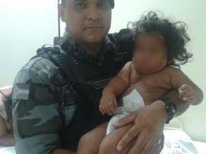 Tenente Ewerton Dias com um dos bebês nos braços, após o resgate (Foto: Marques Santos/Arquivo Pessoal)