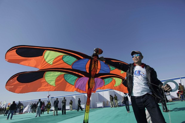 Homem segura pipa em formato de libélula durante festival na Índia (Foto: Ajit Solanki/AP)