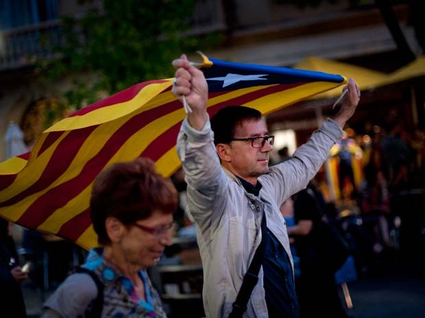 Homem segura bandeira idependentista da Catalunha ao andar pelas ruas de Barcelona na noite desta domingo (27) (Foto: AFP PHOTO / JORGE GUERRERO)