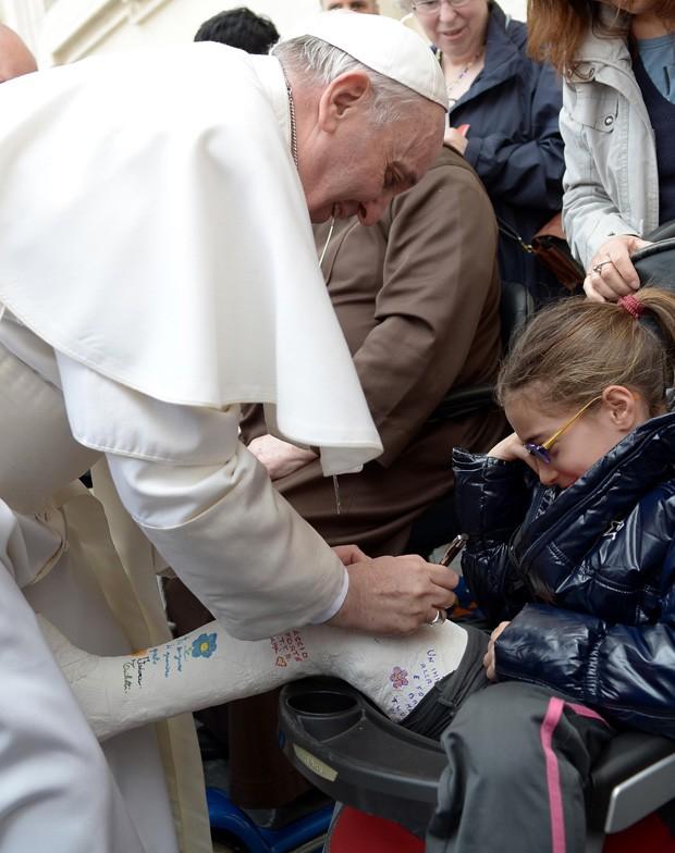 Papa Francisco autografa gesso de jovem na Praça São Pedro (Foto: Osservatore Romano/AFP)