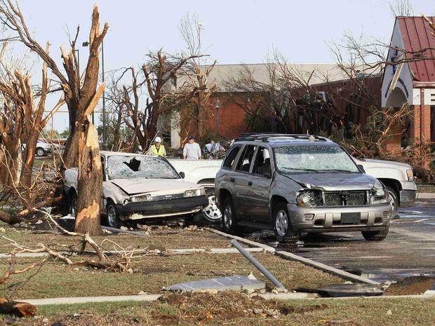 Pessoas andam por carros destruídos por tornado em rua de El Reno, Oklahoma, neste sábado (1º)  (Foto: Bill Waugh/Reuters)
