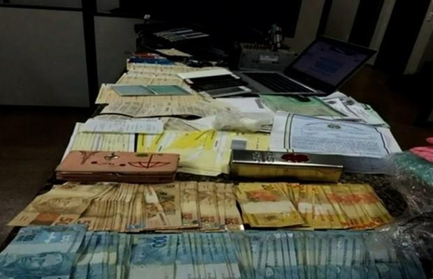 Polícia apreendeu com suspeito dinheiro, drogas, arma, cheques e diversos documentos (Foto: Reprodução/TV Anhanguera)