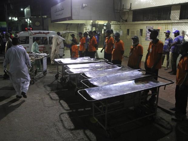 Funcionários de hospital aguardam a chegada de feridos após a explosão em santuário no Paquistão (Foto: Fareed Khan/AP)