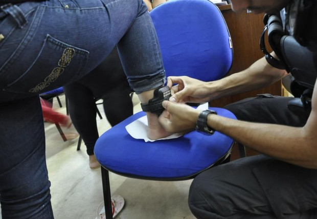Agente penitenciário põe tornozeleira eletrônica em preso no Mato grosso (Foto: Divulgação/Sejudh-MT)
