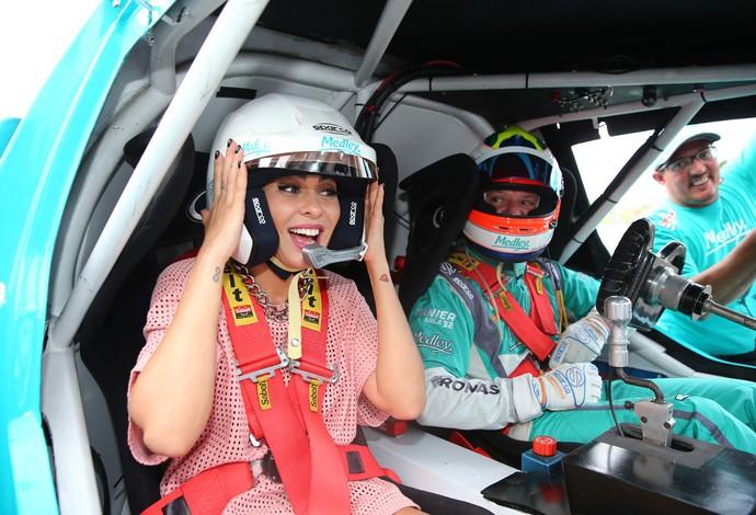 Alinne Rosa tenta soltar a voz no banco do carona de Rubens Barrichello (Foto: Divulgação)