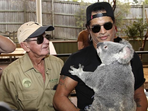Músico Slash segura coala em centro para animais em Brisbane, na Austrália (Foto: Tertius Pickard/AP)
