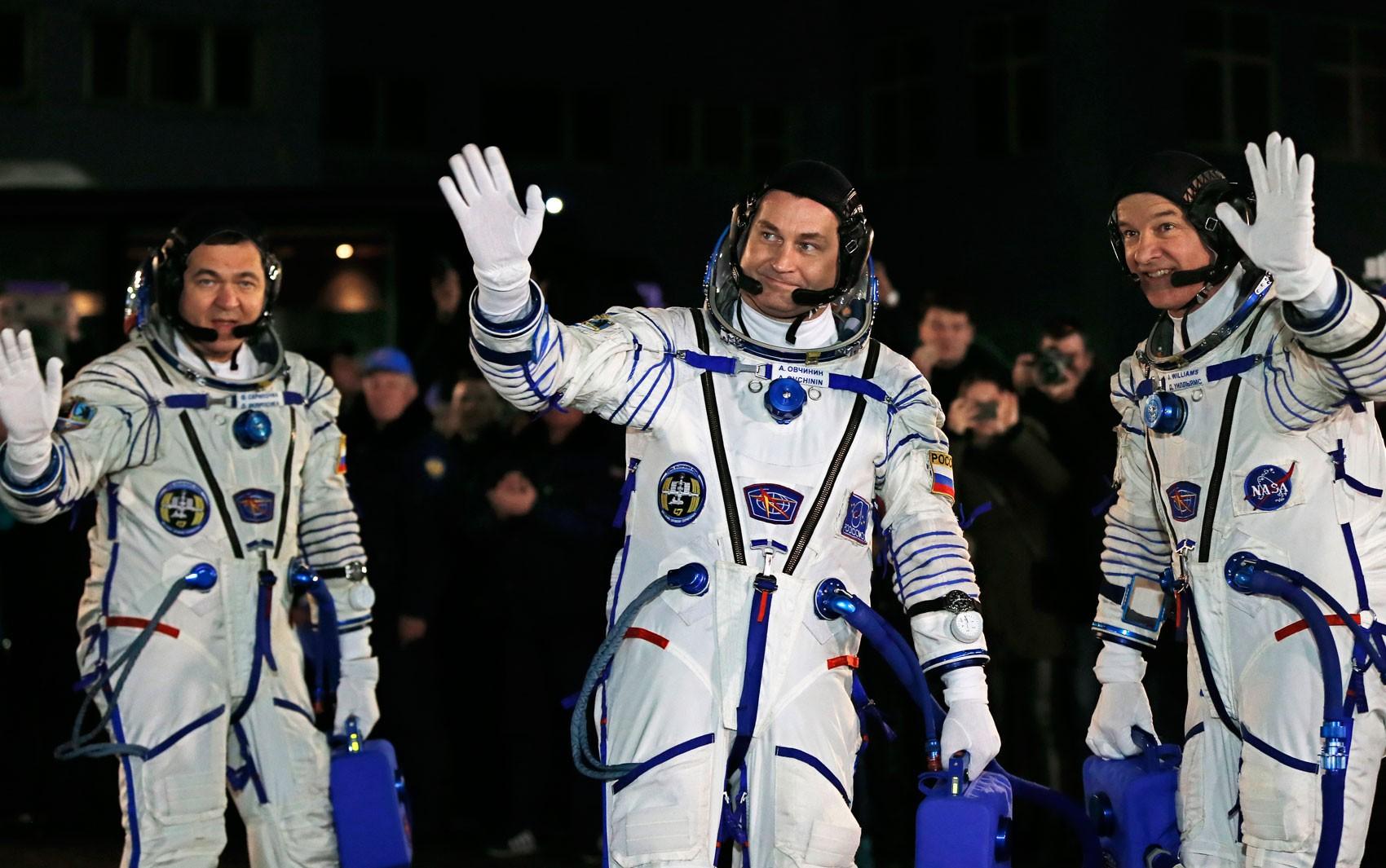 Os astronautas russos Alexey Ovchinin (esquerda) e Oleg Skripochka (direita) e o americano Jeffrey Williams acenam ao se preparar para o lançamento da Soyuz rumo à Estação Espacial Internacional, no Cazaquistão, na sexta (18) (Foto: AFP Photo/Yuri Kochetkov)