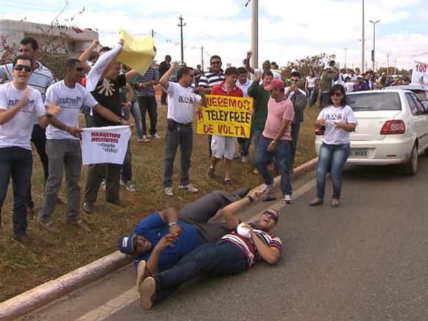 Manifestantes ligados à Telexfree mostram cartazes e deitam em pista de acesso ao aeroporto de Brasília (Foto: TV Globo/Reprodução)
