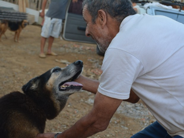 """Antonio abraça cachorro que sobreviveu a parvovirose e agora vive em """"vilarejo"""" em Mogi das Cruzes (Foto: Jamile Santana/ G1)"""