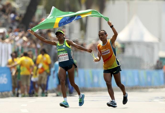Descrição da imagem: Edneusa e seu guia festejam o bronze com a bandeira do Brasil (Foto: REUTERS/Jason Cairnduff)