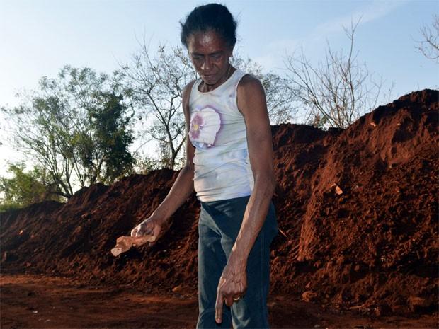 Moradora segura suposto pedaço de osso humano nas mães em estrada de Ribeirão Preto (Foto: Clayton Castelani/ SP)