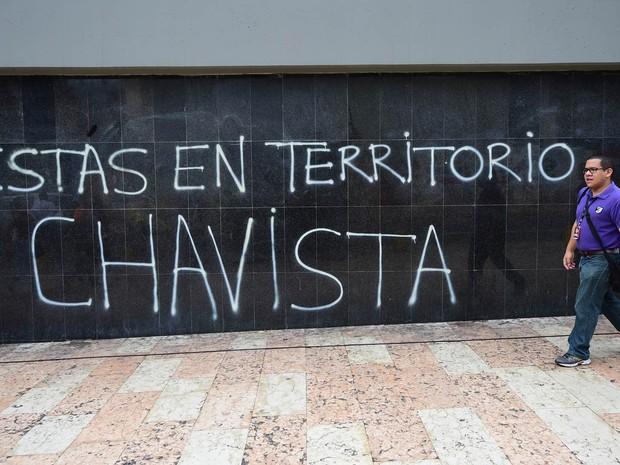Homem passa por uma pichação que em frente à Assembleia Nacional da Venezuela, em Caracas, que diz: 'Você está em território chavista', no dia em que a oposição se instala como maioria no Congresso venezuelano (Foto: Ronaldo Schemidt/AFP)