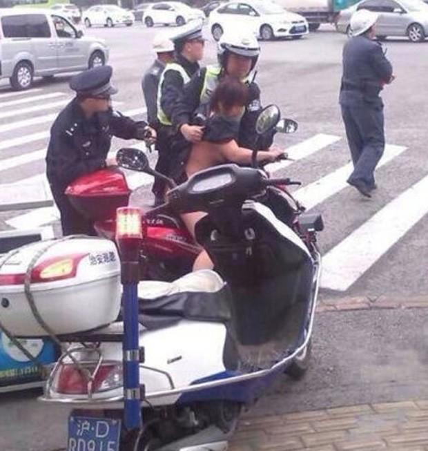 Polícia teve trabalho para dominar chinesa vista pilotando moto sem roupa  (Foto: Reprodução/Weibo/Surabaya Police)