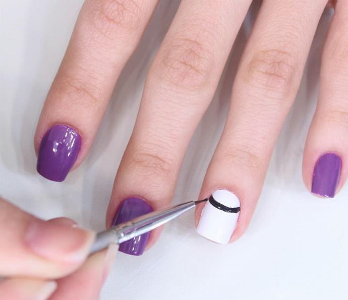 Com a tinta de tecido ou esmalte preto e um pincel fino (nº000) faça um risco no formato de meia-lua virado para a cutícula; (Foto: Arquivo Pessoal)