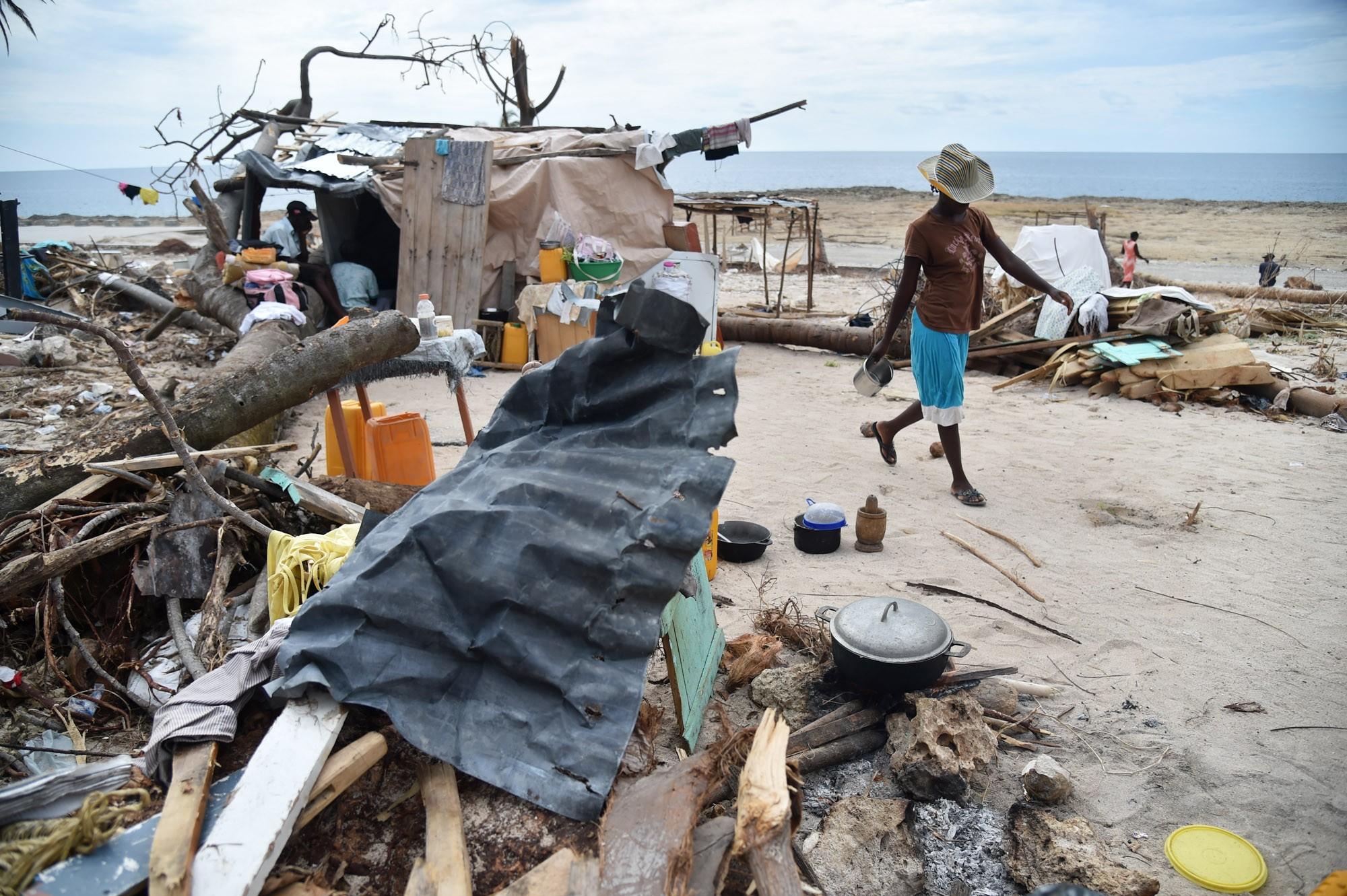 Uma mulher prepara comida perto de sua casa destruída pelo furacão Matthew em Roche-a-Bateaux, no sudoeste do Haiti