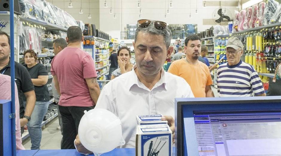 Francisco Feitosa compra peça para o carro usado (Foto: Estadão Conteúdo)