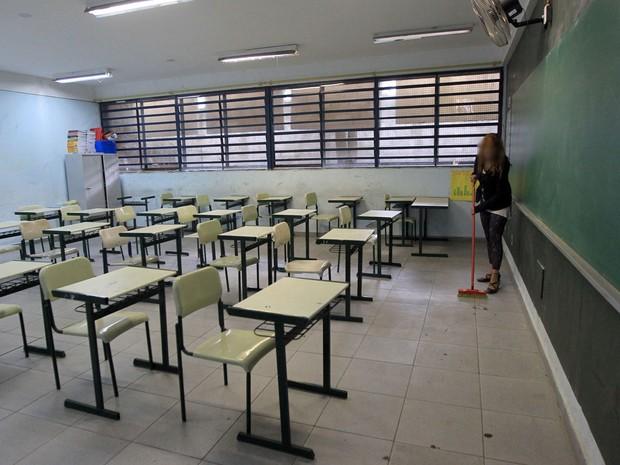 Aluna varre sala de aula usada durante a ocupação na Escola Estadual Brigadeiro Gavião Peixoto (Foto: Werther Santana/Estadão Conteúdo)