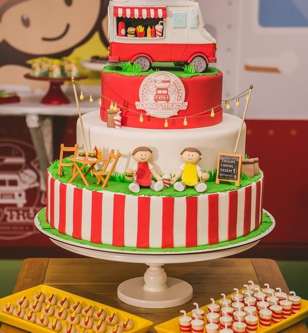 """Foco no bolo: feito de pasta americana, o topo traz o carrinho de foodtruck e, andares abaixo, os dois irmãos, sentados na grama. """"O bolo simula a pracinha em que foodtruck está estacionado, como uma réplica da decoração que fizemos"""", explica o decorador (Foto: Divulgação / Vivian Gradela )"""