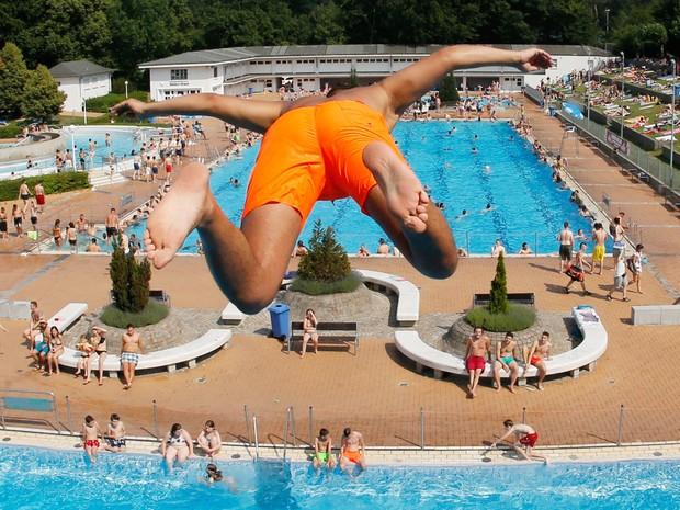 Um garoto salta de uma plataforma de 7,5 metros em uma piscina em Frankfurt, na Alemanha. A onda de calor em toda a Alemanha atingirá o pico no sábado (4), com temperaturas em torno de 40ºC (Foto: Michael Probst/AP)
