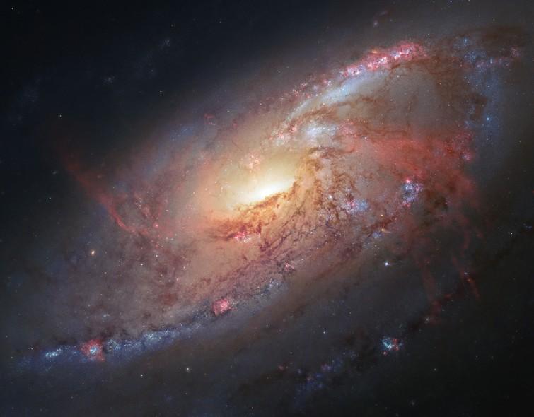 25 anos do Telescópio Espacial Hubble: Messier 106, uma galáxia espiral na constelação de Cão de Caça, a 25 milhões de anos-luz da Terra. Essa galáxia está lentamente caindo em um buraco negro supermassivo em seu centro