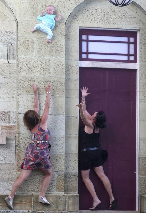 Cynthia Davis e Carol Conroy posam tentando pegar a bebê Matilda Davis em instalação de arte em Sydney nesta segunda-feira (13). Criança estava na verdade no chão – espelhos criaram ilusão de queda (Foto: Rob Griffith/AP)