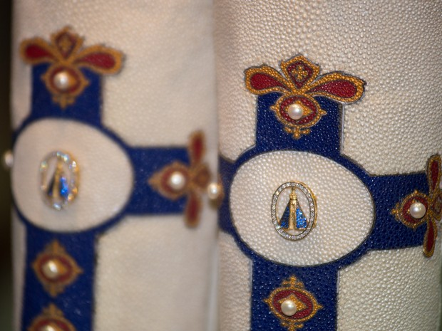Detalhes da joia que estampa Nossa Senhora Aparecida nas botas de couro de arraia   (Foto: Érico Andrade/G1)