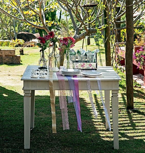 Aproveite o sol da época para fazer o almoço do primeiro dia do ano do lado de fora. Nessa mesa, o charme são as fitas e rendas. Para que não saiam voando, vale prendê-las com adesivo dupla-face (Foto: Cacá Bratke/Casa e Comida)